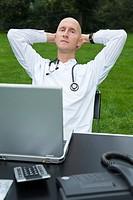 Arzt sitzt mit Laptop an einem Schreibtisch auf einer Wiese und lehnt sich entspannt zurück