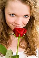 Blondes Mädchen riecht an einer roten Rose