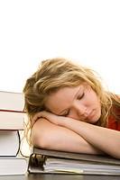 Blondes Mädchen sitzt erschöpft zwischen Büchern an einem Schreibtisch und schläft