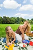 Tochter streckt ihrer Mutter beim Picknick im Park die Zunge heraus