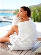 Happy female in a bath robe sitting on a wooden bench