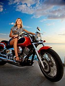 young beautiful blonde outdoors, posing with red motorcycle on quay