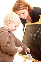 Zweijähriges Kind malt an Tafel und Frau schaut zu