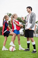 Coach talking to children on soccer team