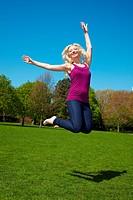 Junge blonde Frau im Park springt hoch in die Luft