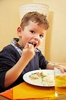 Junge sitzt am Mittagstisch und isst mit Gabel