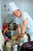Koch steht am Waschbecken mit Kochgeschirr