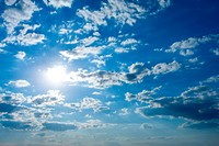 Cloudscape with sun in blue sky