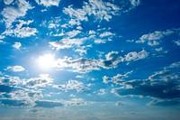 Cloudscape with sun in blue sky