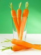 Three carrots in a glass in front of a green background.