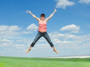 pretty young woman jumping on green grass over blue sky