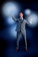 Businessman interacting with holographic binary globes
