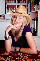 Smiling blonde woman with cowboy hat in a cafe
