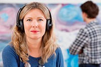 Mid adult woman wearing headphones in gallery