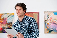 Young man using digital tablet in art gallery