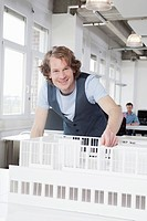Germany, Bavaria, Munich, Architect with architectural model, colleagues working in background