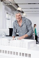 Germany, Bavaria, Munich, Man standing with architectural model in office (thumbnail)