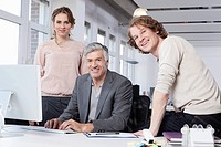 Germany, Bavaria, Munich, Men and woman using computer in office, smiling, portrait