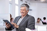 Germany, Bavaria, Munich, Mature man using digital tablet, colleagues working in background