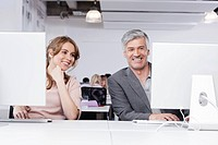 Germany, Bavaria, Munich, Man and woman using computer in office, smiling