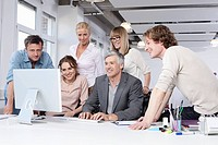 Germany, Bavaria, Munich, Men and women using computer in office, smiling