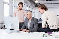 Germany, Bavaria, Munich, Men and woman using computer in office, smiling