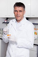 Germany, Bavaria, Munich, Scientist with liquid in beaker for medical research in laboratory