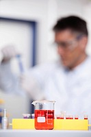 Germany, Bavaria, Munich, Red liquid in beaker, scientist doing medical research in background