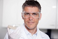 Germany, Bavaria, Munich, Scientist holding liquid in petri dish for medical research in laboratory