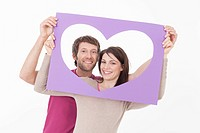 Couple looking through heart shaped frame