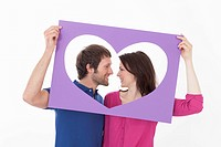 Couple looking at each other behind heart shaped frame