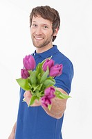 Mid adult man with flowers, smiling, portrait