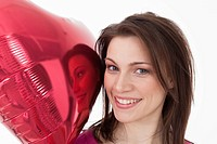 Young woman with heart shaped balloon, portrait