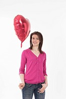 Young woman holding heart shaped balloon, portrait