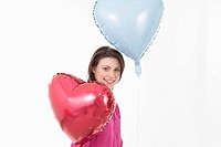 Young woman with heart shaped balloons, portrait