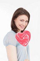 Young woman with heart shaped lollipop, portrait