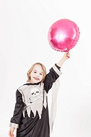 Boy in fancy dress costume with balloon, portrait