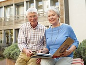 Germany, Cologne, Senior couple with photo album in front of nursing home, portrait