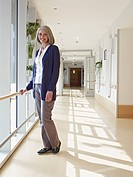 Germany, Cologne, Senior woman standing at corridor in nursing home, portrait