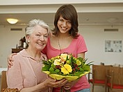 Germany, Cologne, Women holding bouquet in nursing home, smiling, portrait