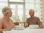 Germany, Cologne, Senior couple sitting at table, smiling