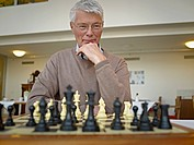 Germany, Cologne, Senior man playing chess in nursing home