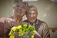 Germany, Cologne, Senior couple with flower bouquet, smiling