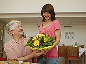 Germany, Cologne, Women holding bouquet in nursing home, smiling