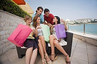 Group of friends with shopping bags posing (thumbnail)