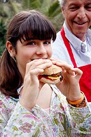 Teenage girl eating a hamburger