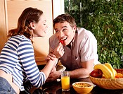 A young couple eating breakfast