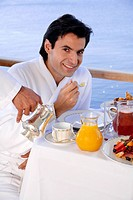 Young man having breakfast on hotel terrace