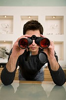 Man with binoculars in eyeglass store