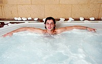 Young man in jacuzzi at a spa